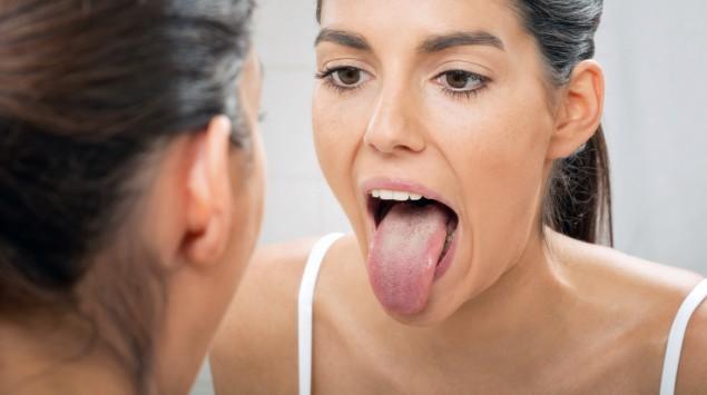 Eine Frau betrachtet ihre Zunge im Spiegel.