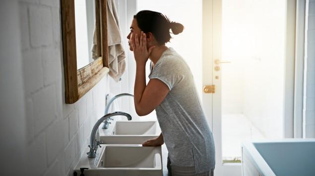 Eine Frau steht am Waschbecken und blickt in den Spiegel.