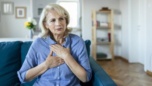 Eine ältere Frau fasst sich an die Brust.