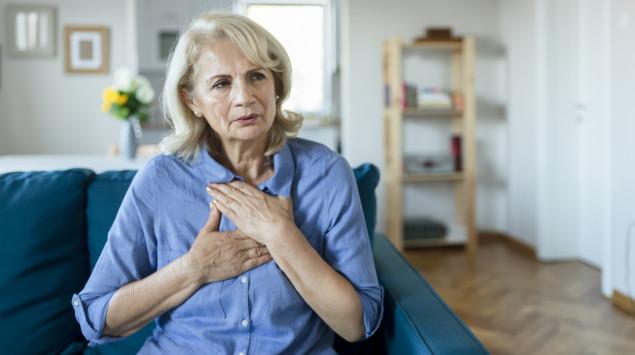 Eine ältere Frau fasst sich an die Brust: Hinter vermeintlichen Herzbeschwerden kann das Roemheld-Syndrom stecken.