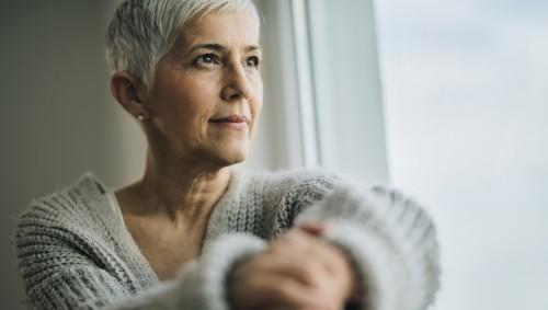 Eine ältere Frau sitzt am Fenster.
