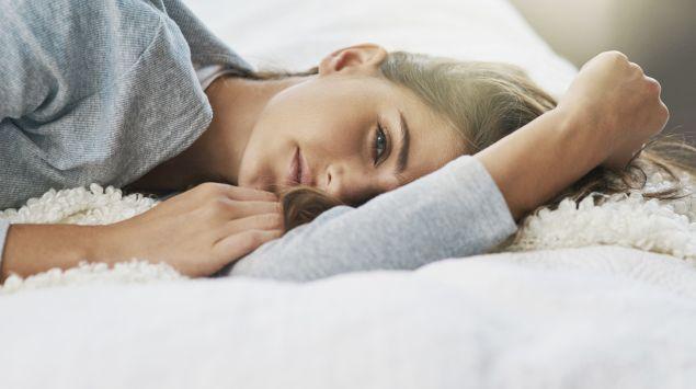 Eine Frau liegt entspannt auf dem Bett.