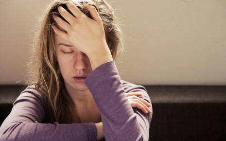 Chronisches Erschöpfungssyndrom: Man sieht eine erschöpft wirkende Frau, die ihren Kopf mit der Hand stützt.