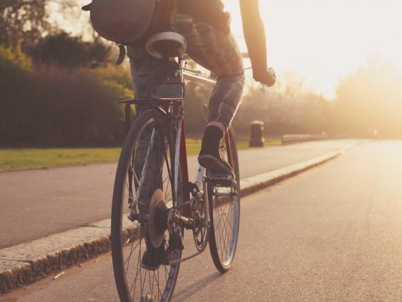 Vitamin D: Eine junge Frau fährt mit dem Rad auf einer Straße.