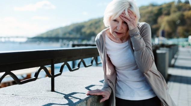 Eine ältere Frau fasst sich an den Kopf und stützt sich an einer Mauer ab.