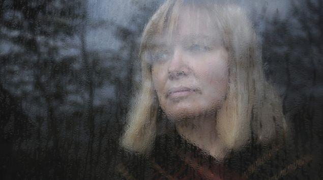 Eine Frau schaut traurig aus dem Fenster.