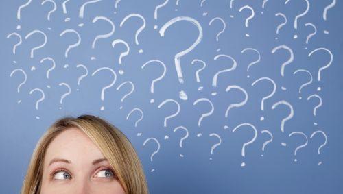 Eine Frau blickt fragend, über ihr mehrere gemalte Fragezeichen.