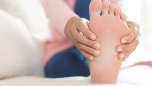Eine Frau sitzt auf dem Bett und umfasst ihren linken Fuß.