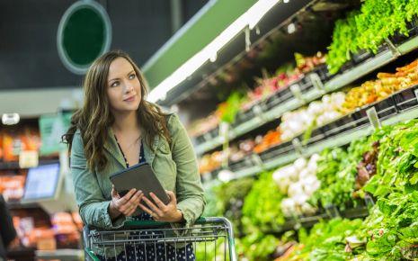 Clean Eating: Eine Frau steht im Supermarkt in der Gemüseabteilung.