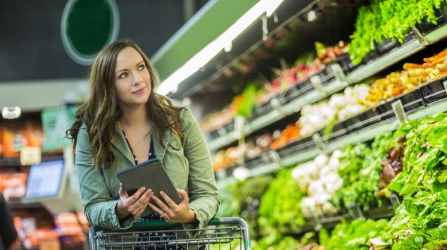 Eine Frau steht im Supermarkt in der Gemüseabteilung.