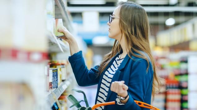 Eine Frau im Supermarkt prüft die Liste der Zusatzstoffe einer Lebensmittelkonserve.