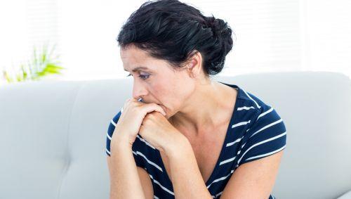 Eine Frau sitzt auf dem Sofa und denkt nach.