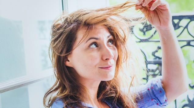 Eine Frau betrachtet skeptisch eine Haarsträhne.