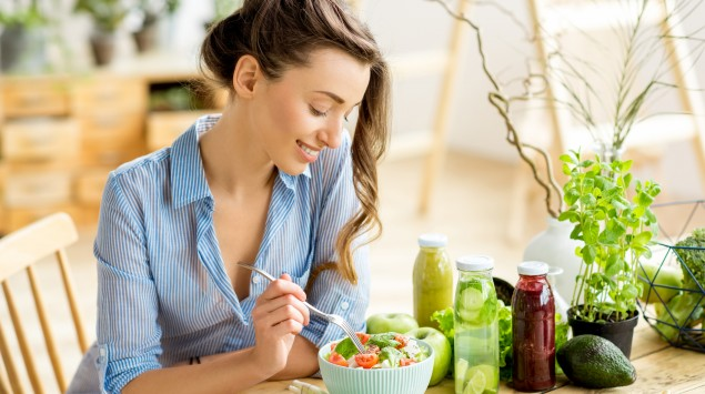 Eine junge Frau sitzt am Tisch und isst.