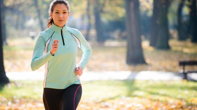 Man sieht eine Frau, die in einem Park joggt.