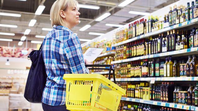Eine Frau steht im Supermarkt vor dem Ölregal.