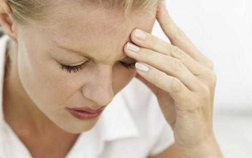 EIne Frau fasst sich vor Schmerzen an den Kopf.