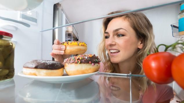 Eine Frau holt sich Donuts aus dem Kühlschrank.