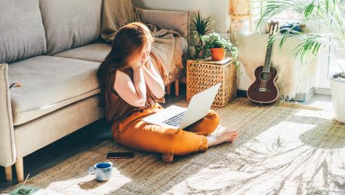 Eine junge Frau sitzt auf dem Fußboden und schaut auf ihren Laptop.