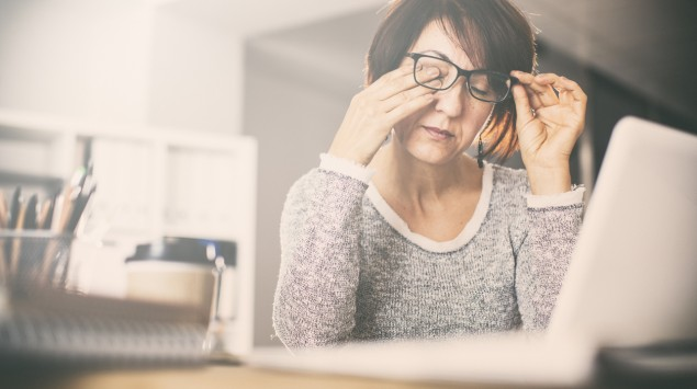 Eine Frau sitzt am Laptop und reibt sich die Augen.
