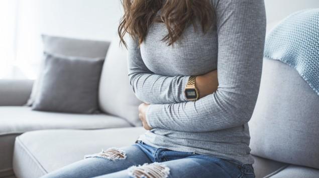 Eine Frau sitzt auf dem Sofa und hat die Arme über den Bauch gelegt.