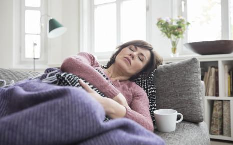 Washilft gegen Durchfall? Eine Frau liegt auf dem Sofa und hält sich den Bauch.