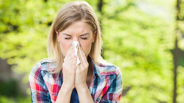 Eine junge Frau putzt sich die Nase.