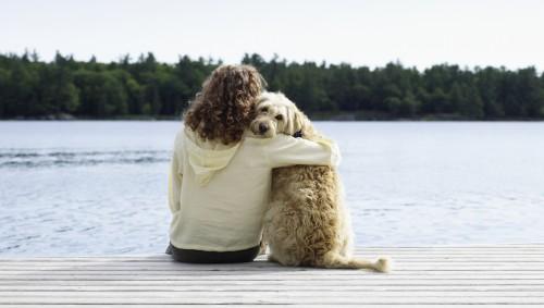 Eine Frau und ein Hund sitzen nebeneinander auf einem Holzsteg an einem Gewässer; die Frau hat den Arm um den Hund gelegt.