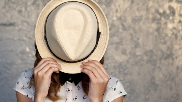 Eine junge Frau hält sich einen Hut vors Gesicht.