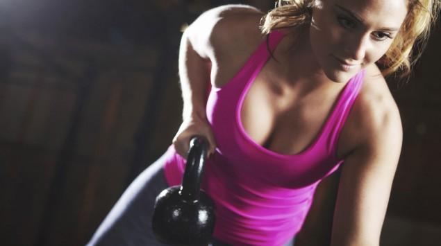 Das Bild zeigt eine Frau, die eine Übung mit einer Kettlebell macht.