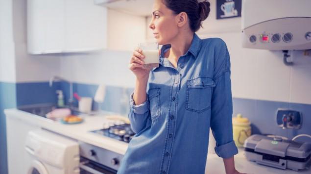 Eine Frau stützt sich auf die Küchenarbeitsplatte und hält ein Glas Milch in der Hand.