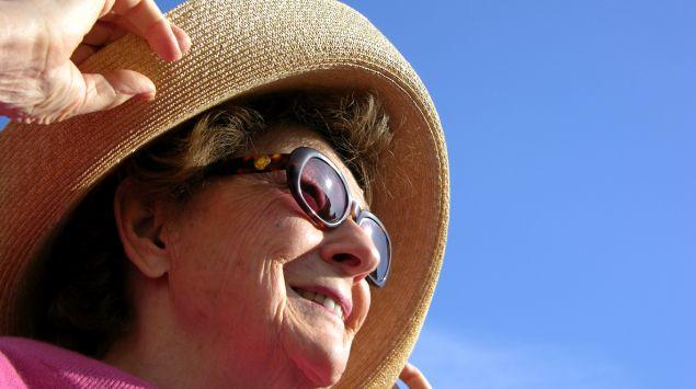 Eine Frau trägt Hut und Sonnebrille.