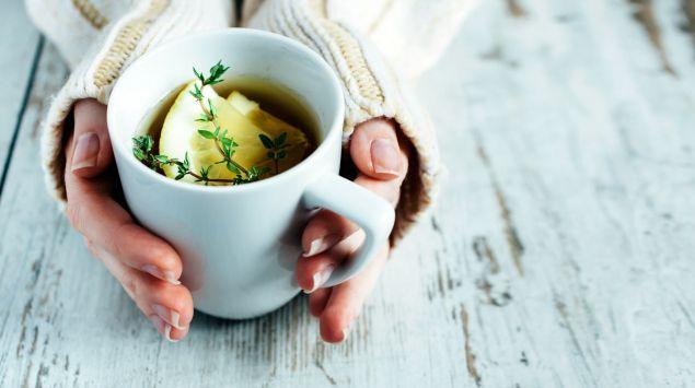 Das Bild zeigt eine Frau, die eine Tasse Tee in den Händen hält.