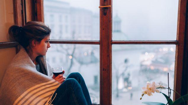 Eine Frau sitzt am Fenster und trinkt ein Glas Rotwein.