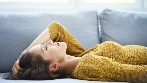 Eine müde Frau liegt auf dem Sofa.