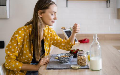 Eine Frau sitzt in der Küche und isst Müsli