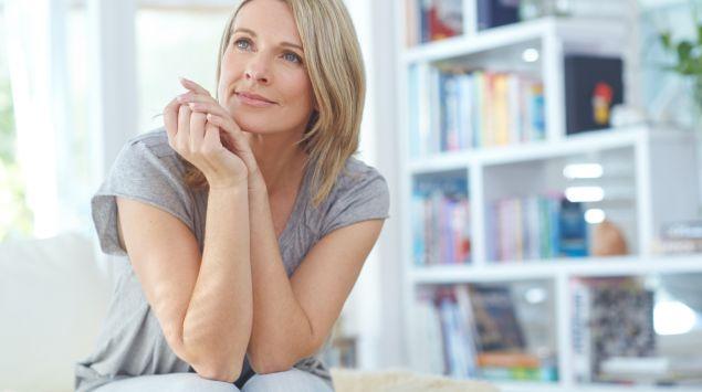 Eine nachdenklich wirkende Frau sitzt im Wohnzimmer auf einem Sofa.