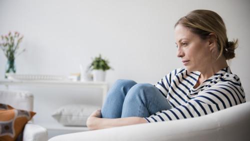 Eine nachdenklich aussehende junge Frau sitzt auf dem Sofa.