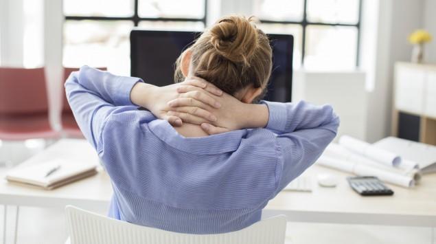 Eine Frau sitzt am PC und verschränkt die Hände im Nacken.