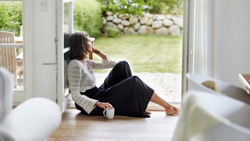 Eine nachdenklich aussehende junge Frau sitzt auf dem Fußboden an der offenen Terassentür.
