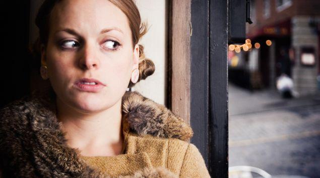 Eine Frau steht an einer Straßenecke und hat große Angst.