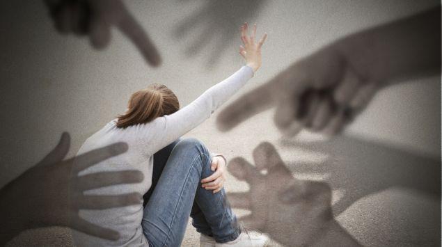 Eine Frau kauert am Boden, schemenhaft dargestellt Hände greifen nach ihr.