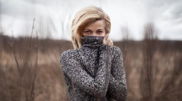 Neurodermitis ist ungefährlich, aber oft belastend: Eine Frau verbirgt ihr Gesicht mit einem Pullover.