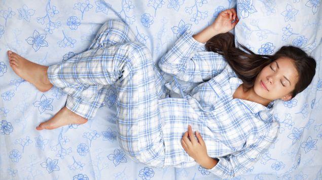 Eine Frau liegt in einem Pyjama auf dem Bett.