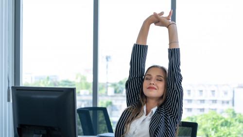 Eine Frau sitzt am Schreibtisch und reckt sich.