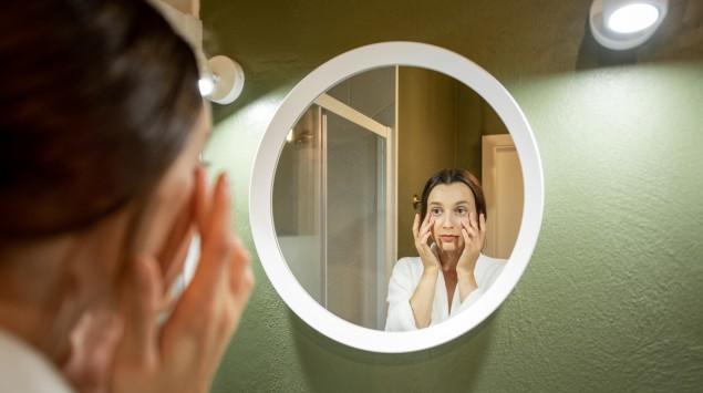 Eine Frau schaut prüfend in den Spiegel: Wenn Augen oder die Haut gelb gefärbt sind, ist zu viel Bilirubin im Körper vorhanden.