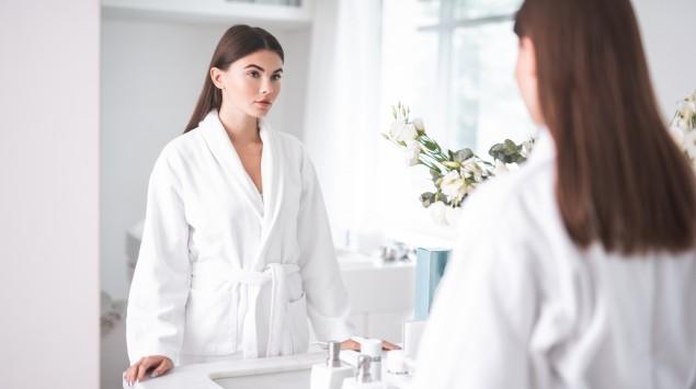 Eine Frau steht im Badezimmer und schaut in den Spiegel.