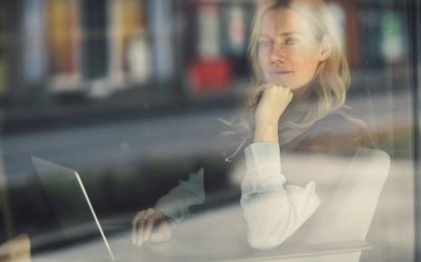 Burnout-Syndrom: Eine Frau blickt nachdenklich aus dem Fenster.
