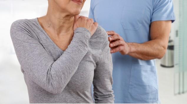 Verdachtsdiagnose Fibromyalgie: Man sieht eine Frau beim Arzt, die an ihre schmerzende Schulter greift.
