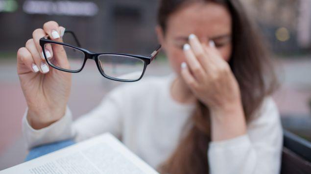 Eine Frau hat ihre Brille abgenommen und drückt die Finger gegen den Nasenrücken.